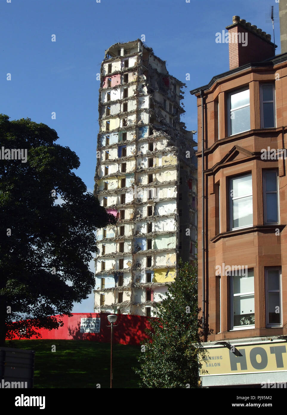 A partially demolished high rise block of flats standing next to a red  sandstone tenement building in Glasgow. - Stock Image