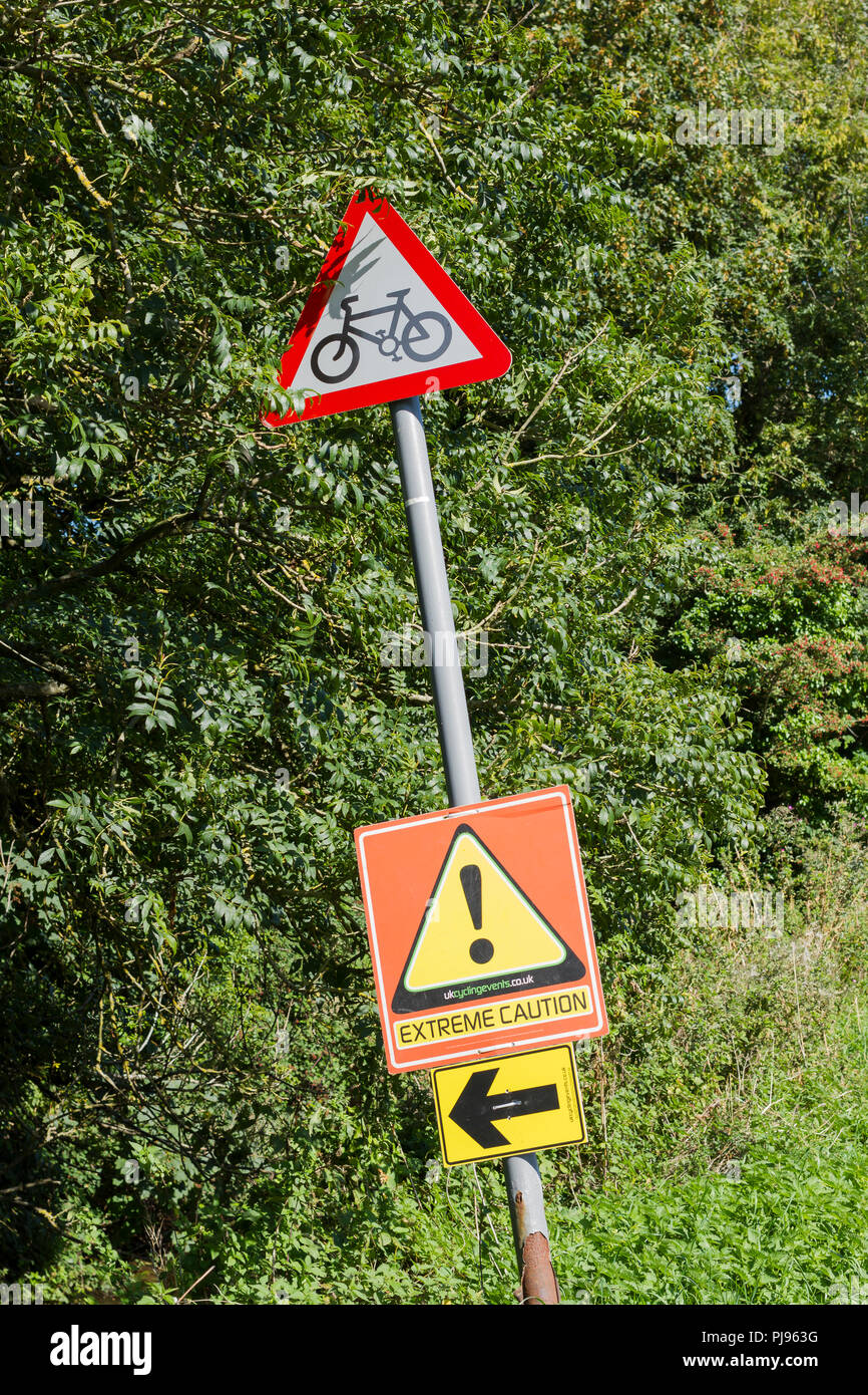 Red triangular cycling road sign in the Dorset countryside, England, UK - Stock Image