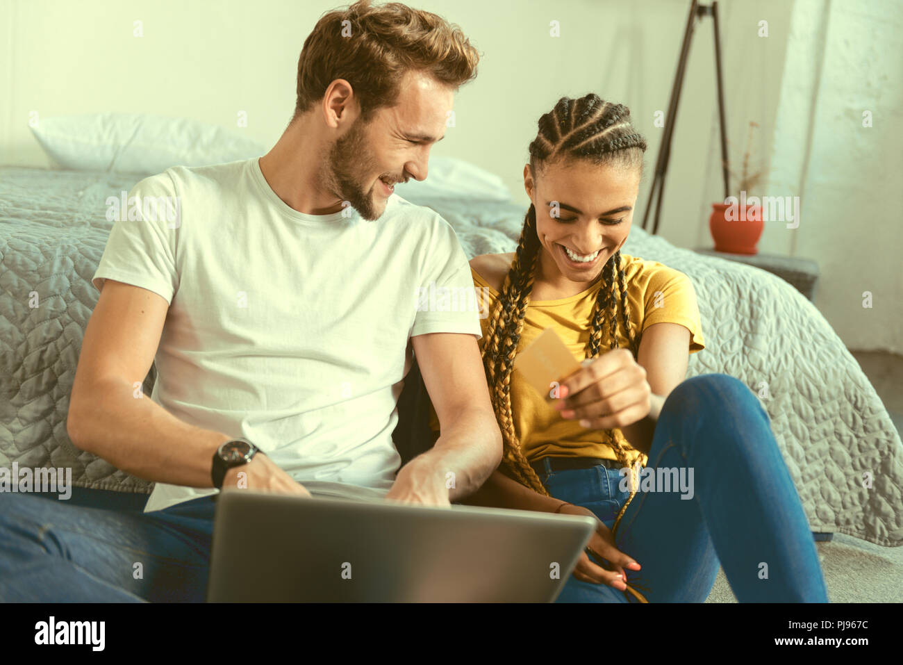 Radiant couple laughing while making online shopping - Stock Image