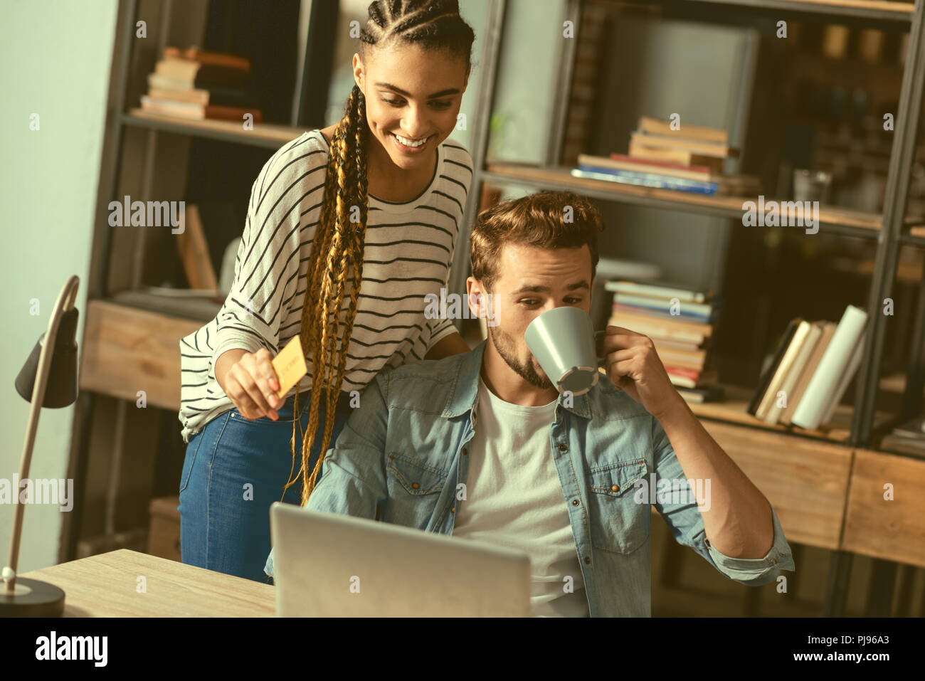 Relaxed girlfriend and boyfriend doing online shopping together - Stock Image