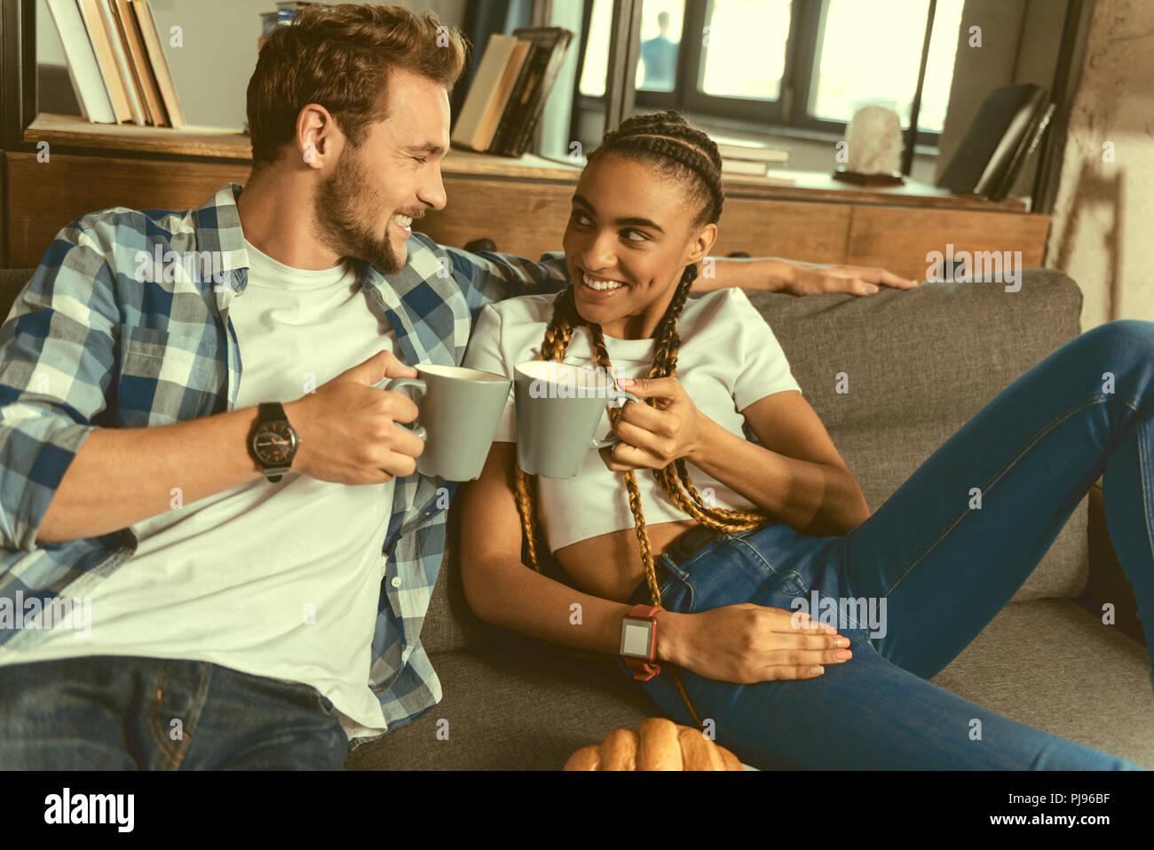 International couple enjoying tea together - Stock Image