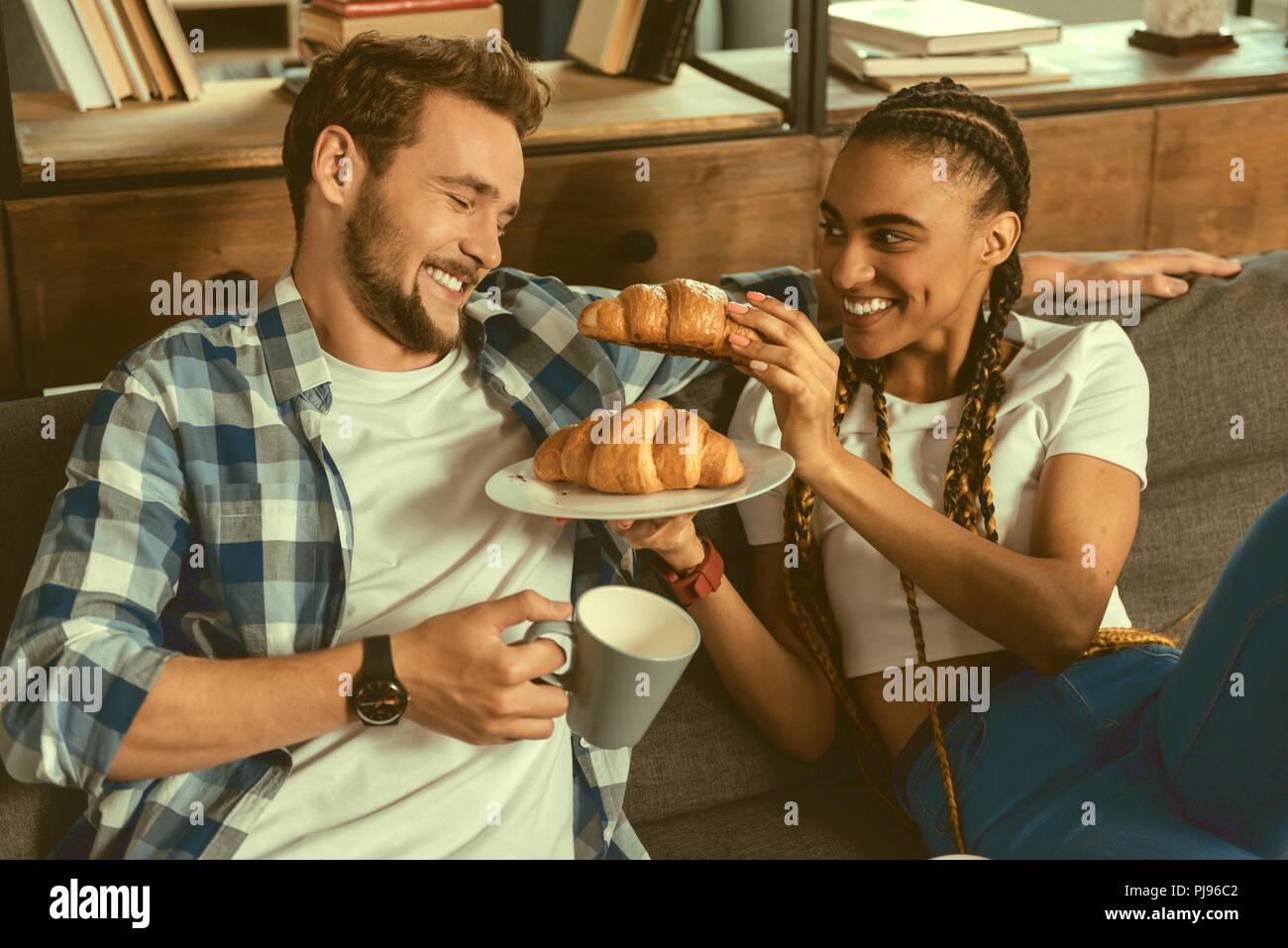 Loving girl treating boyfriend to croissant - Stock Image