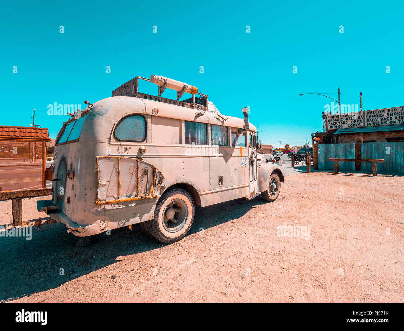 Vintage bus used to travel the world left behind in the desert - Stock Image
