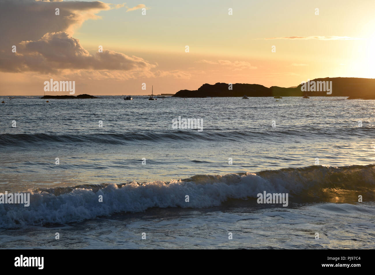 Sunset over Trearddur Bay near Holyhead, Anglesea, North Wales with sunlight reflecting off the water and waves. Orange sky silhouette landscape seasc - Stock Image