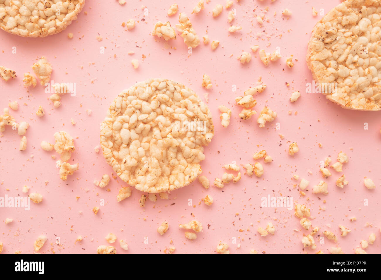 Flat lay crunchy rice cakes on pastel pink background, overhead top down view - Stock Image