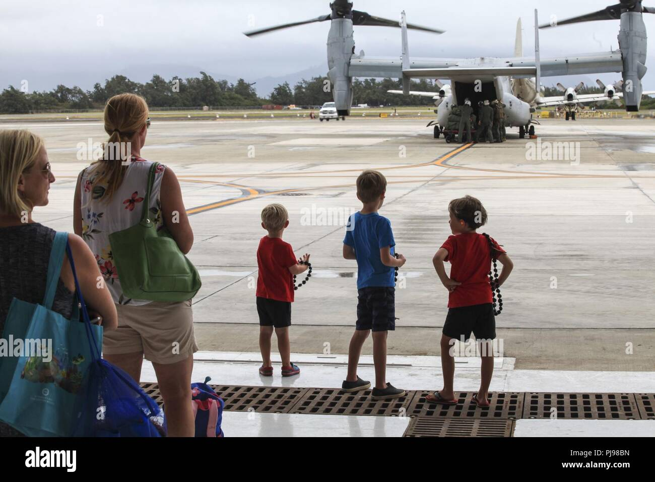 Families wait for their loved ones on MV-22B Ospreys assigned to Marine Medium Tiltrotor Squadron 363 (VMM-363) to disembark, Marine Corps Air Station Kaneohe Bay, Marine Corps Base Hawaii, July 7, 2018. MV-22B Ospreys assigned to VMM-363 is part of the squadron's scheduled relocation to their new command, Marine Aircraft Group 24, 1st Marine Aircraft Wing. VMM-363's capabilities will significantly enhance the Marine Corps' ability to perform humanitarian assistance and disaster response, respond to crises and fulfill other alliance roles in the Indo-Pacific region. Decisions regarding the arr Stock Photo