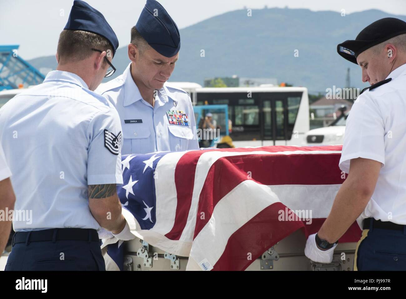 U.S. service members assigned to the Defense POW/MIA Accounting Agency (DPAA), drape a transfer case with the American flag during a repatriation ceremony, Da Nang, Socialist Republic of Vietnam, July 8, 2018. The ceremony was conducted in support of DPAA's mission to provide the fullest possible accounting of our missing personnel to their families and the nation. - Stock Image