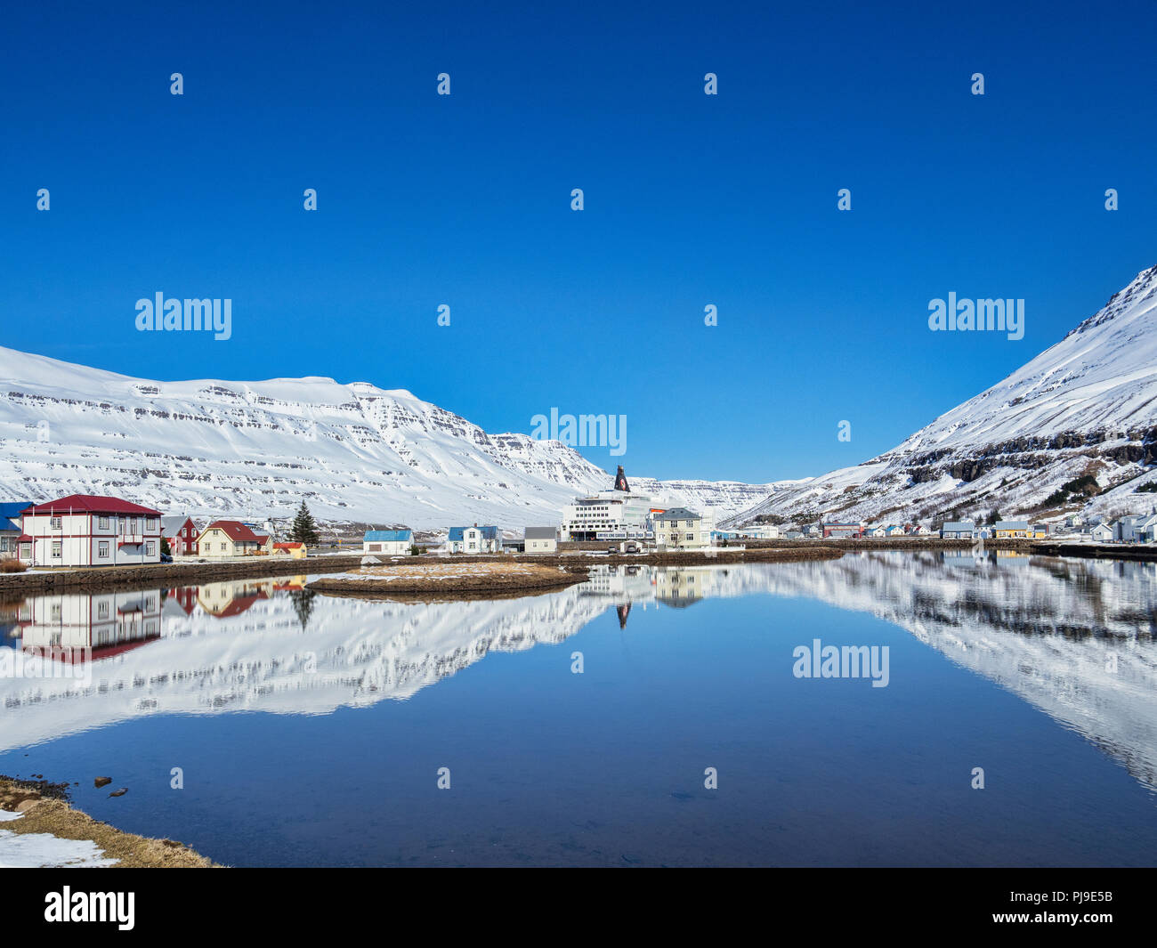 11 April 2018; Seydisfjordur, East Iceland - The village reflected in the fiord, and the Smyril Line ferry MS Norrona. - Stock Image