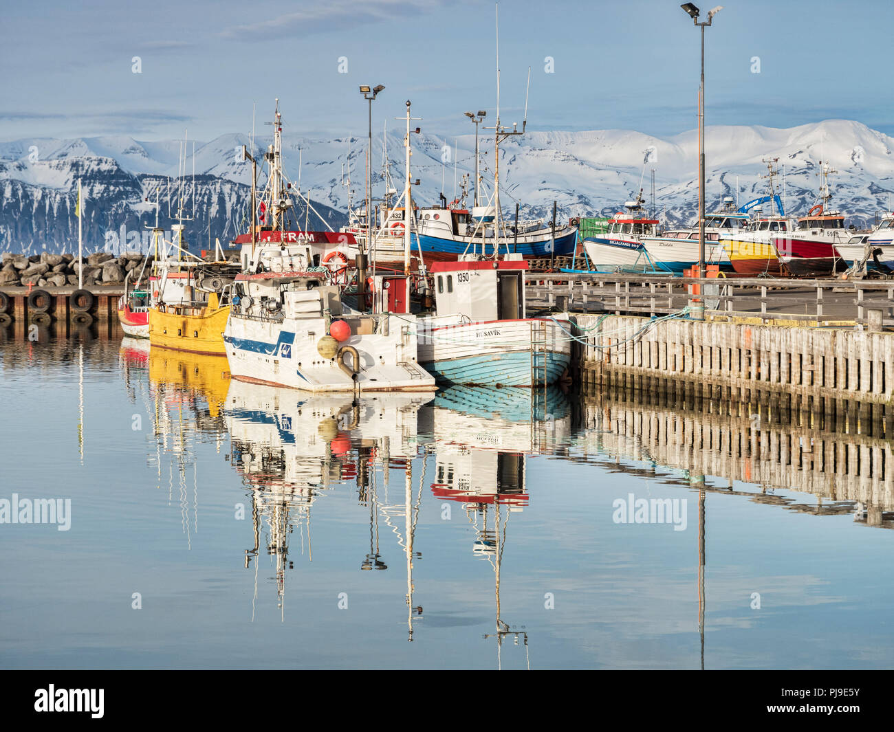 13 April 2018: Husavik, North Iceland - Fishing boats in the harbour on a bright spring day. - Stock Image
