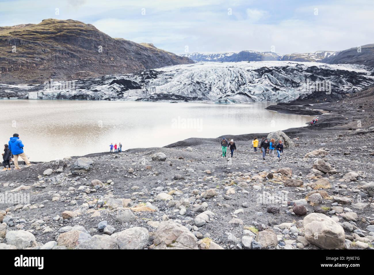21 April 2018:  South Iceland - Tourists at Solheimajokull Glacier Tongue and glacial lake. - Stock Image