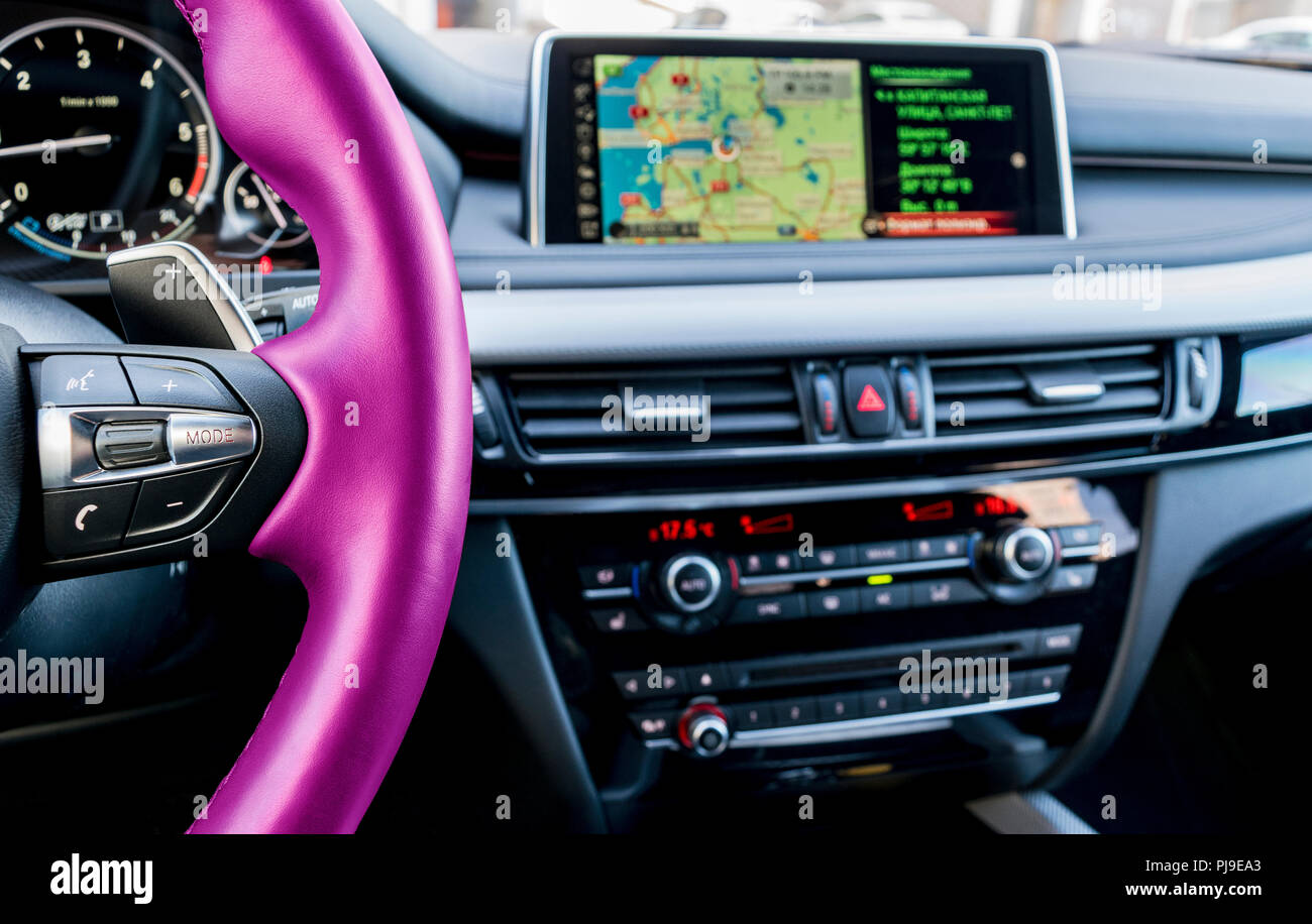 Modern car interior. Pink steering wheel with media phone control buttons. Navigation screen. Multimedia system background. Car interior details. Car  - Stock Image