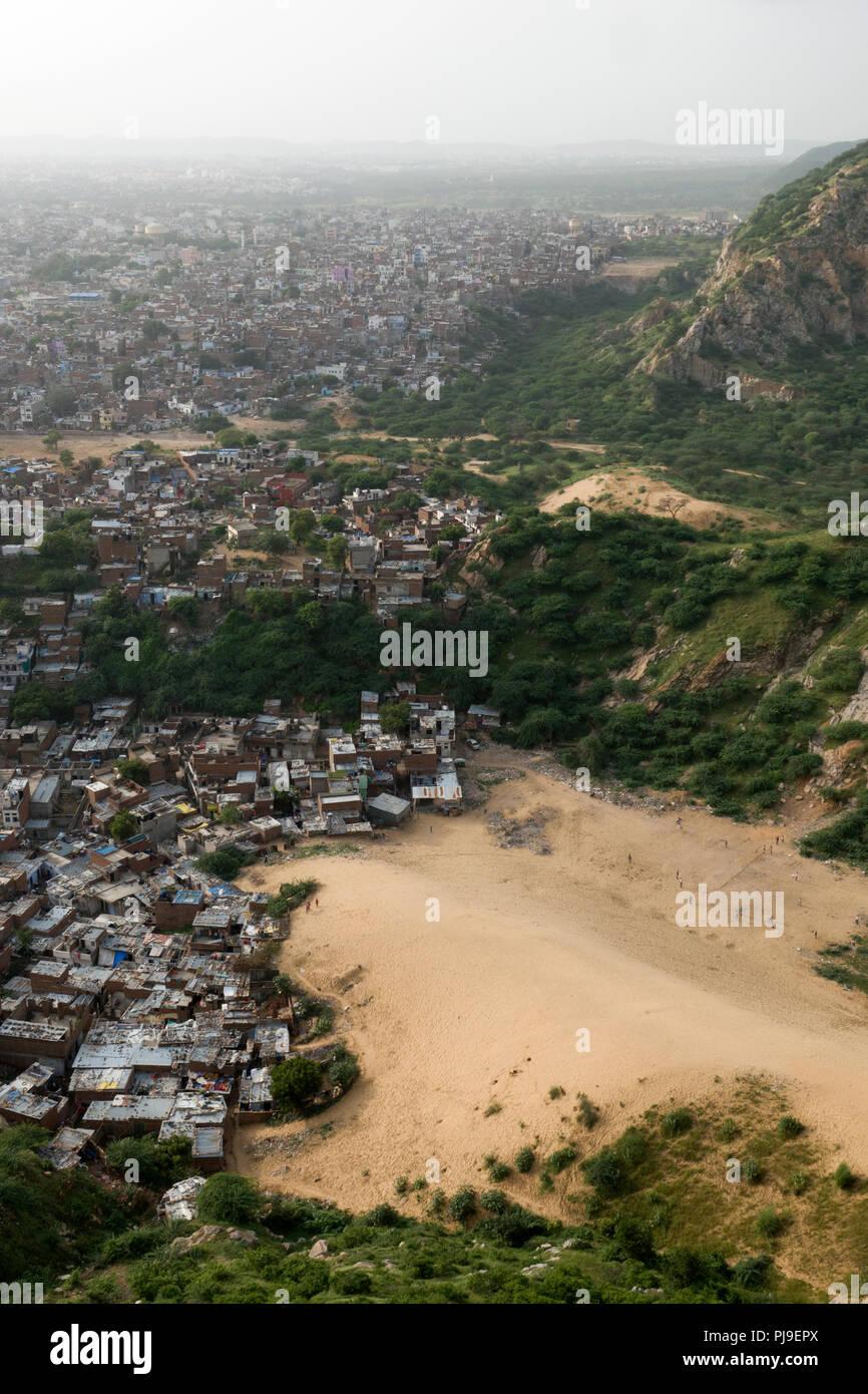 Slum area next to sand dunes at base of Aravalli Hills in Jaipur, Rajasthan, India - Stock Image