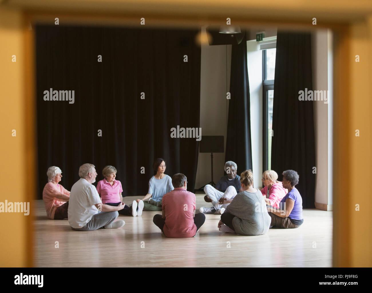 Active seniors meditating in circle - Stock Image