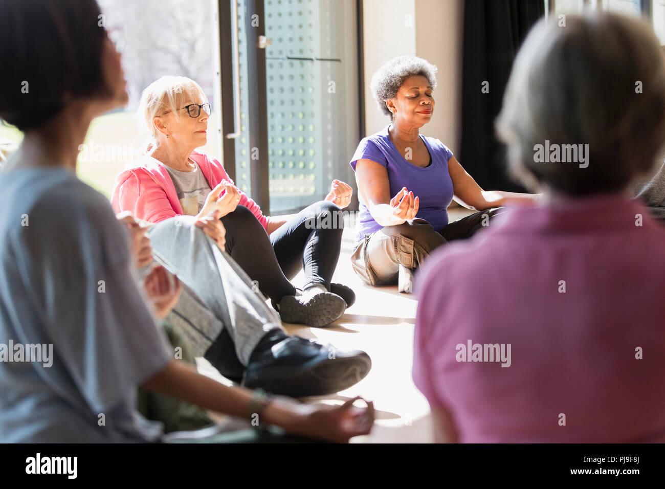 Serene active seniors meditating in circle - Stock Image