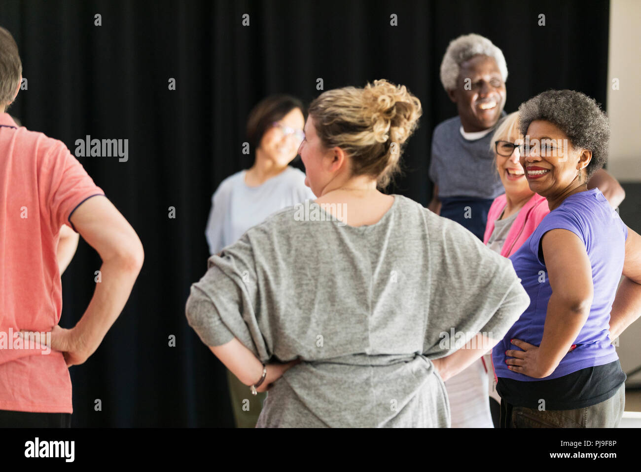 Smiling active seniors exercising in circle - Stock Image