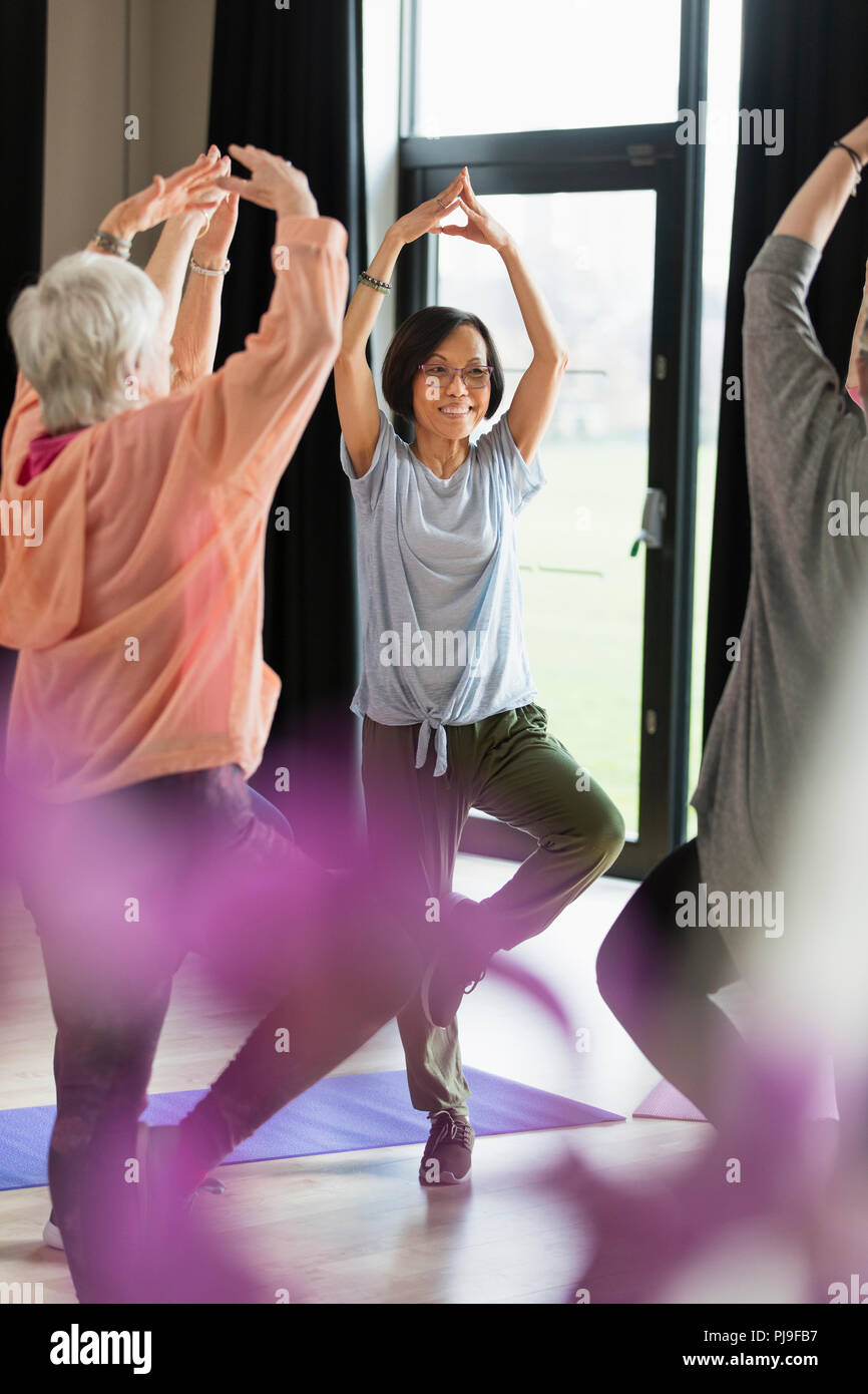 Smiling active senior woman exercising, practicing yoga tree pose Stock Photo