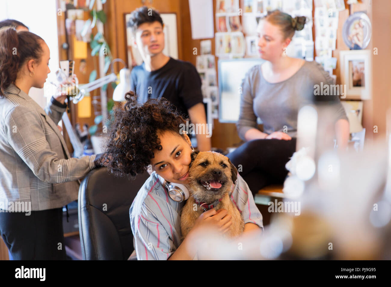 Portrait creative female designer with dog in office - Stock Image