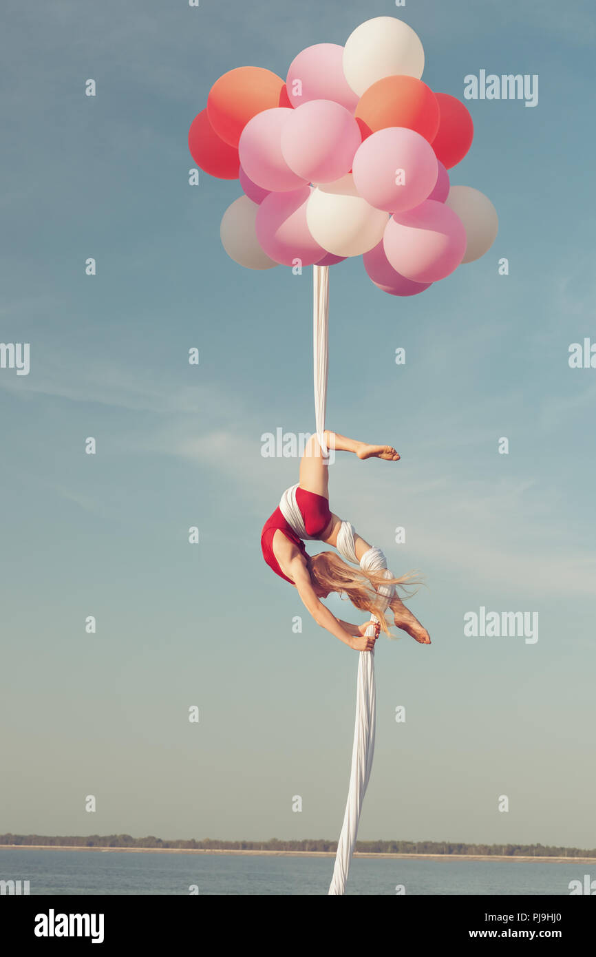 Girl does acrobatic stunts. She floats in the air on balloons. Stock Photo