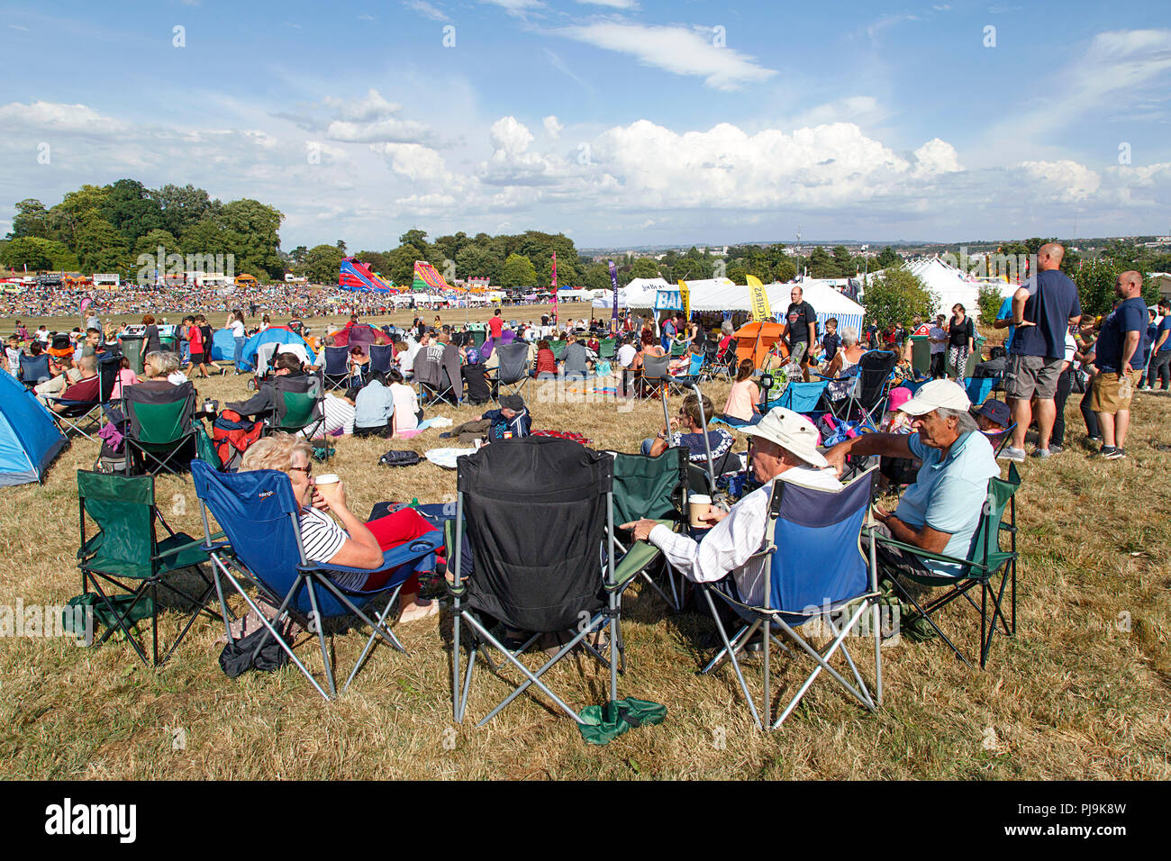 Bristol, UK: August 09, 2018: A group of mature adults sit on camping chairs at Bristol International Balloon Fiesta. - Stock Image