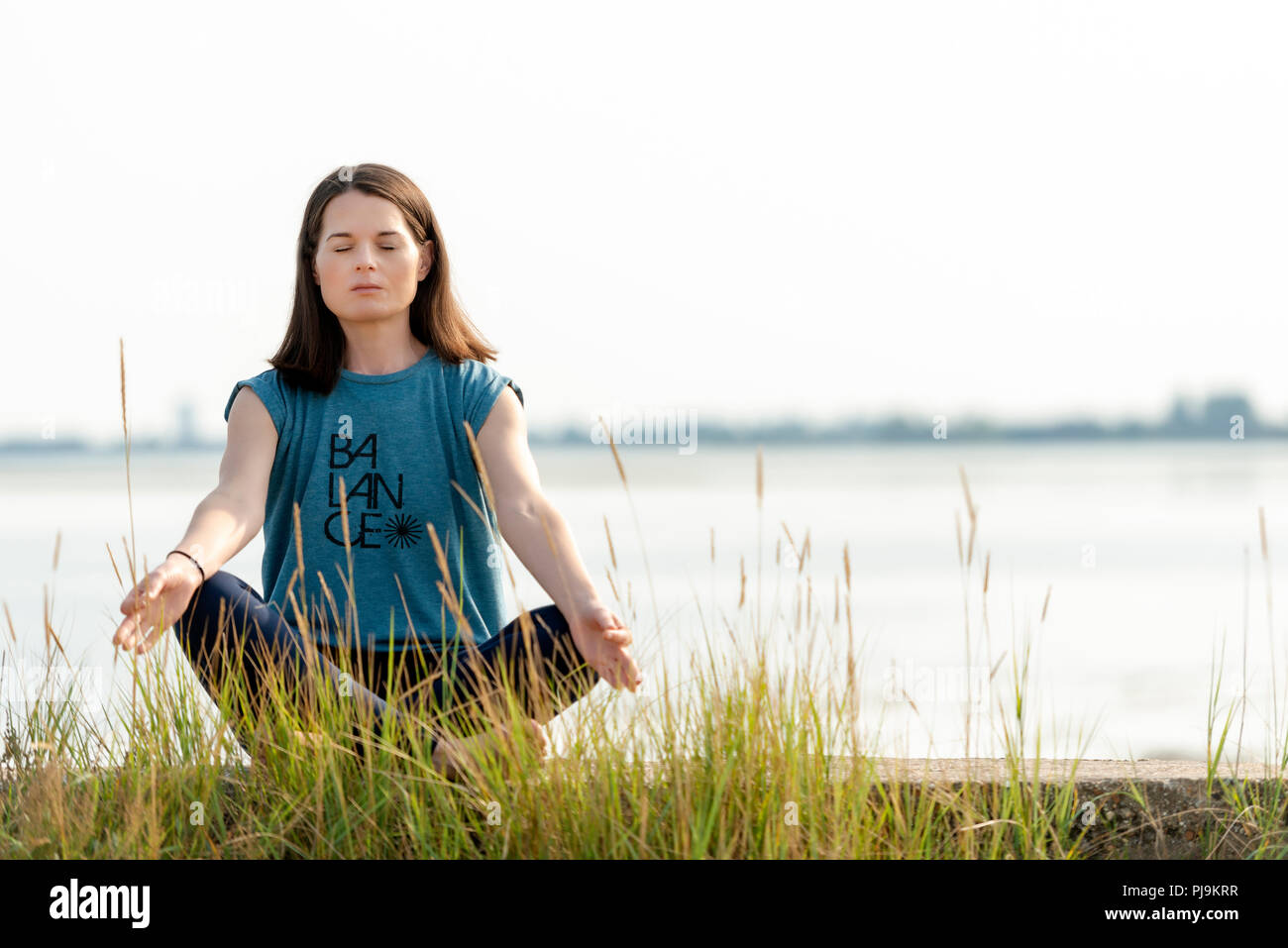 woman sitting crossed legged and meditating - Stock Image