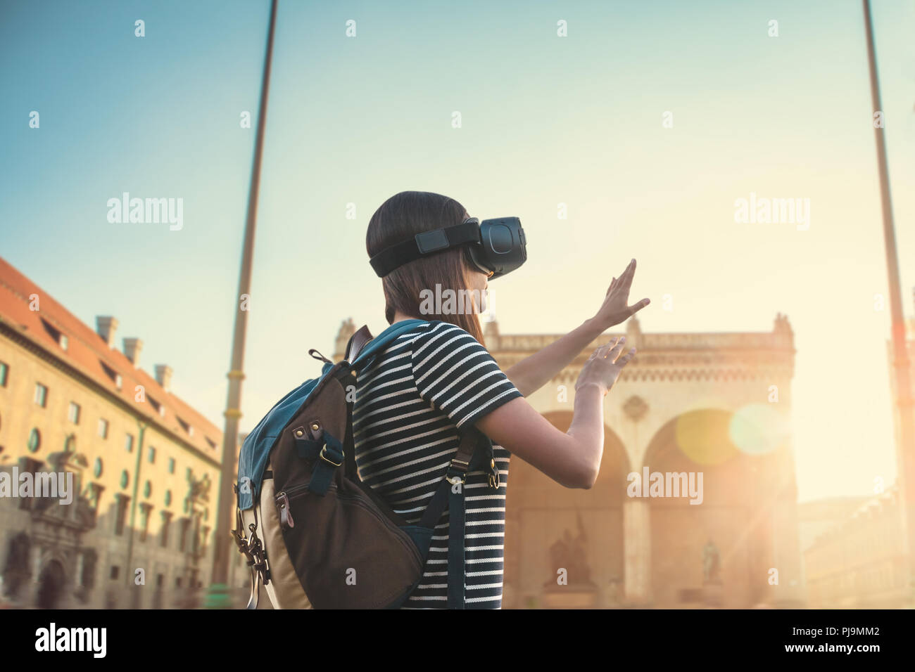 Girl tourist in glasses virtual reality. Virtual trip to Germany. The concept of virtual tourism. In the background is the square on Leopoldstrasse in Munich. Stock Photo