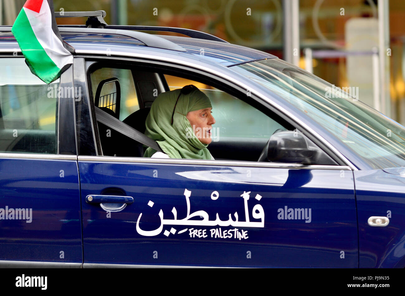 Woman wearing a headscarf driving a car with a Palestinian flag and 'Free Palestine' printed on the door, central London, England, UK. 2018 - Stock Image
