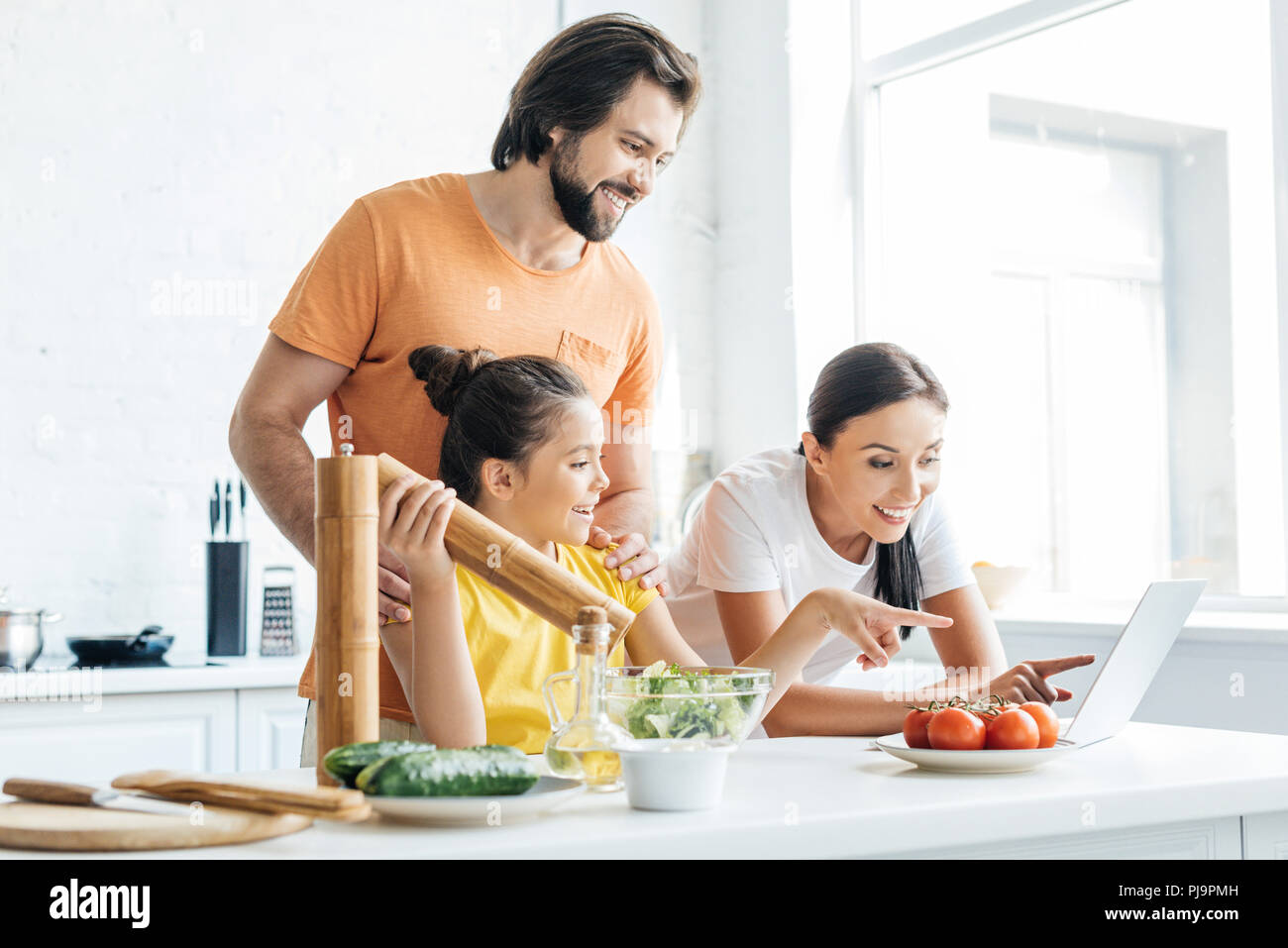 beautiful young family using laptop while cooking at kitchen - Stock Image