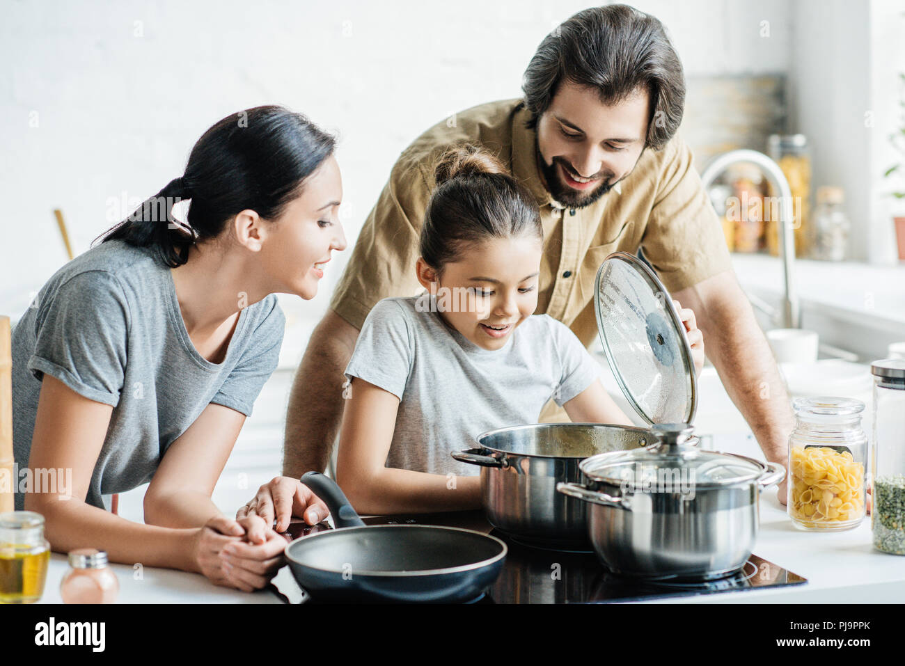 smiling young family cooking together at kitchen - Stock Image