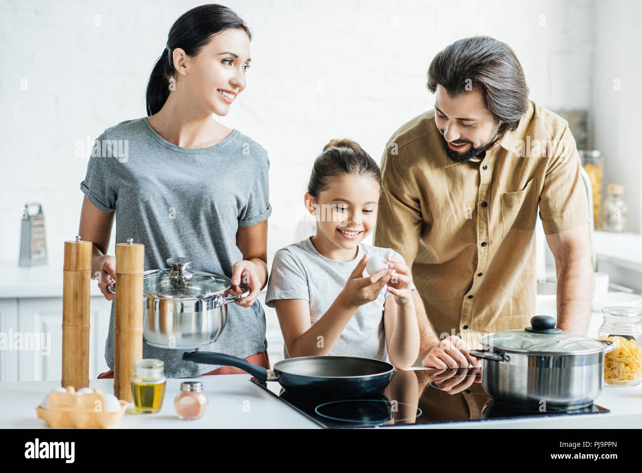 smiling family with little daughter cooking omelet at kitchen Stock Photo