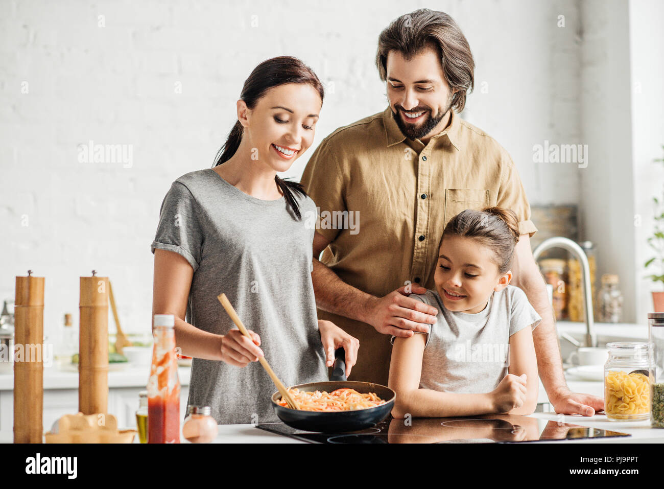 beautiful family with little daughter cooking omelet at kitchen - Stock Image
