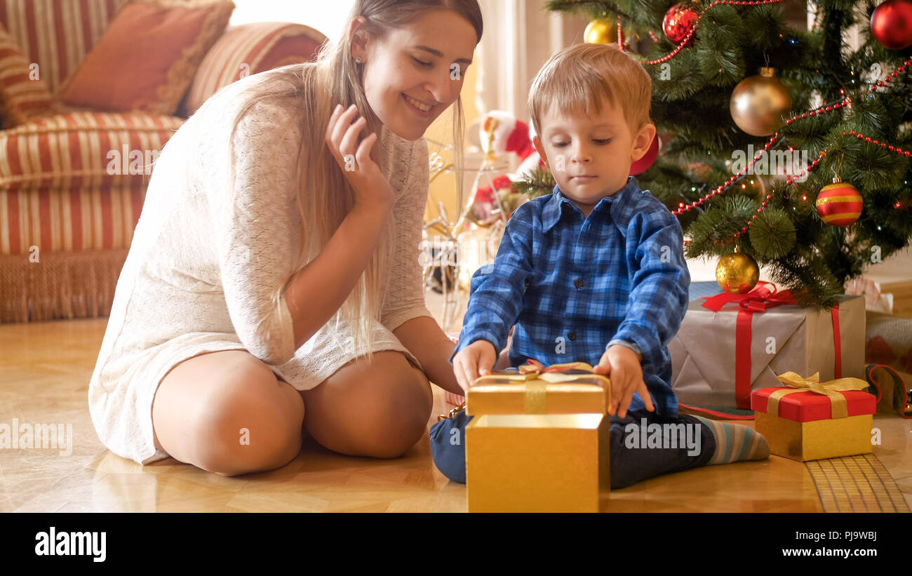 Happy young mother and toddler son are excited of Christmas gifts ...