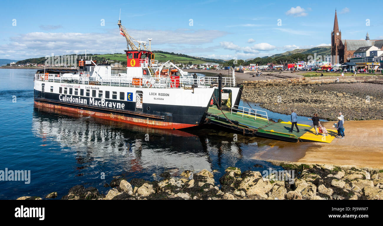 Passengers boading the CalMac Loch Riddon Ferry to the Isle of Cumbrae (Millport) via the ramp at the mainland seaside town of Largs. - Stock Image