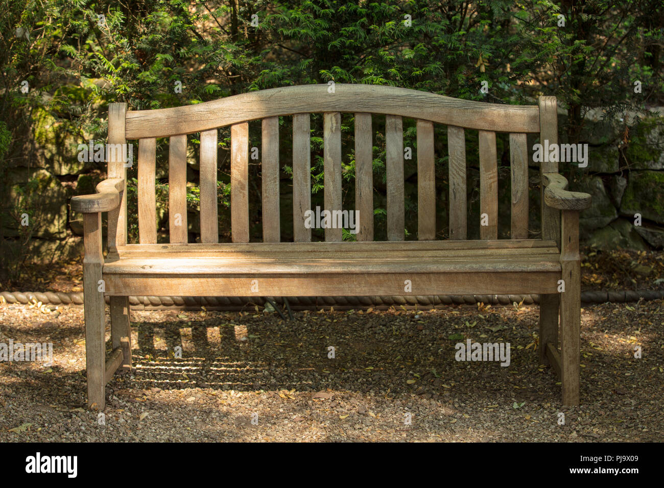 Hardwood garden bench feature and focal point in an inspirational garden design. Handmade outdoor furniture of craftmanship as ornament and to be used - Stock Image
