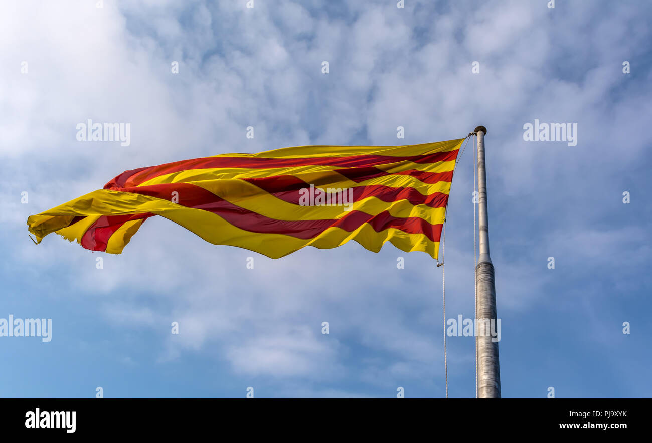 Flag of Catalonia waving in the breeze against blue sky. The flag is called The Senyera (flag in Catalan) and consists of four red stripes on yellow - Stock Image
