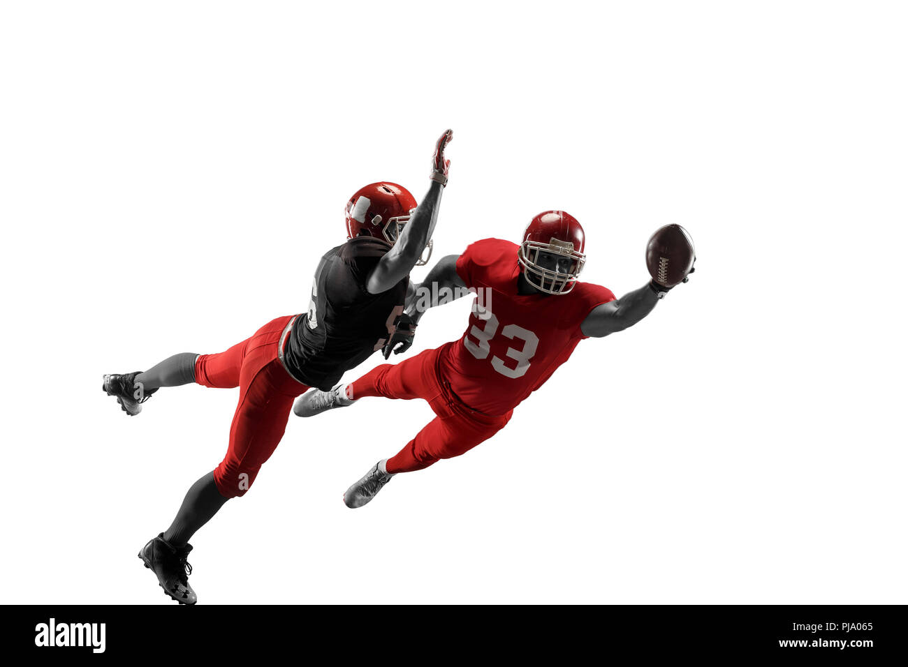 Active two american football player isolated on white background. Fit caucasian men in uniform with ball jumping over studio background in jump or motion. Human emotions and facial expressions concept. scramble concepts - Stock Image