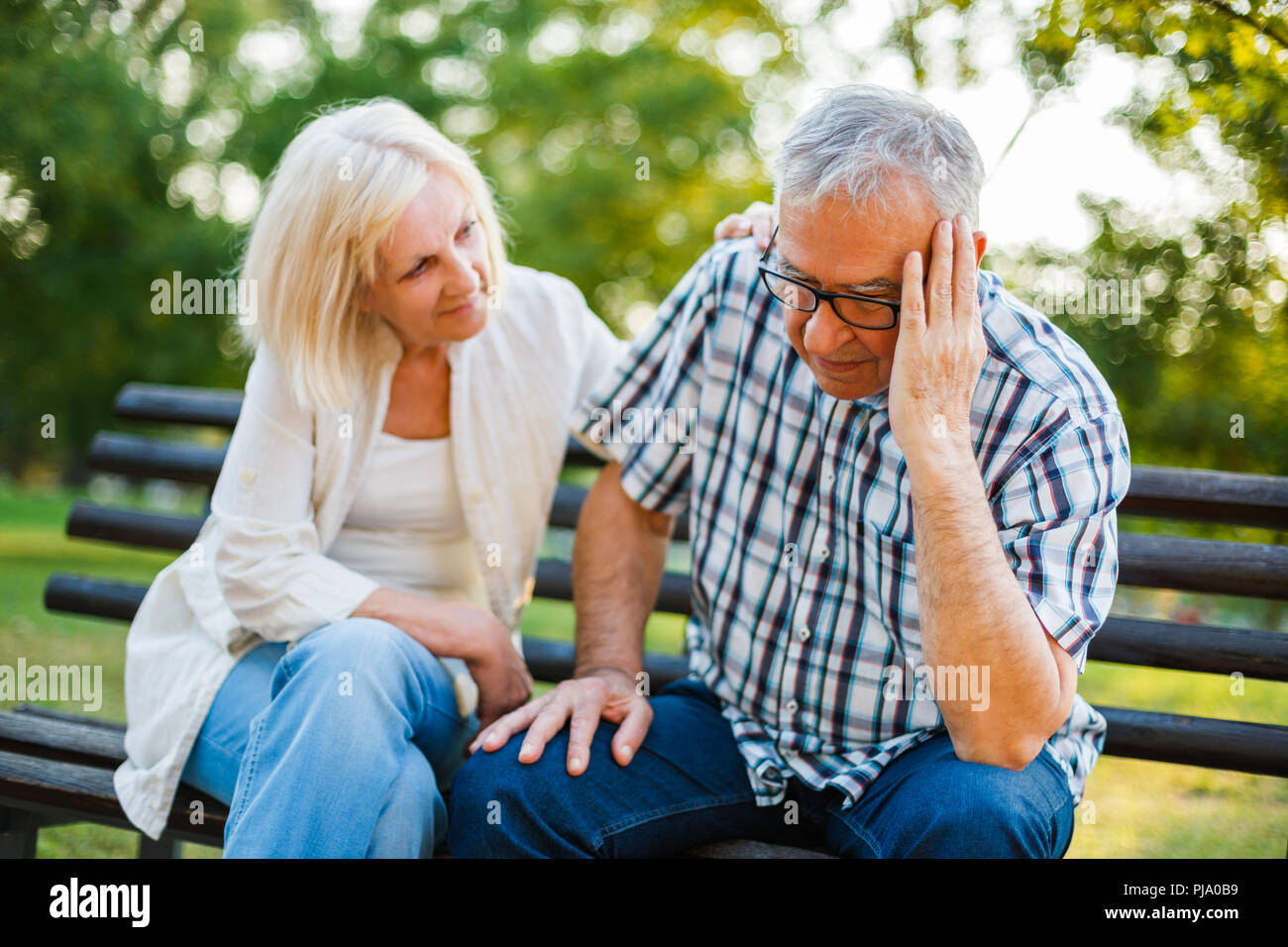 Senior man is sad and depressed. Friend is consoling him. - Stock Image