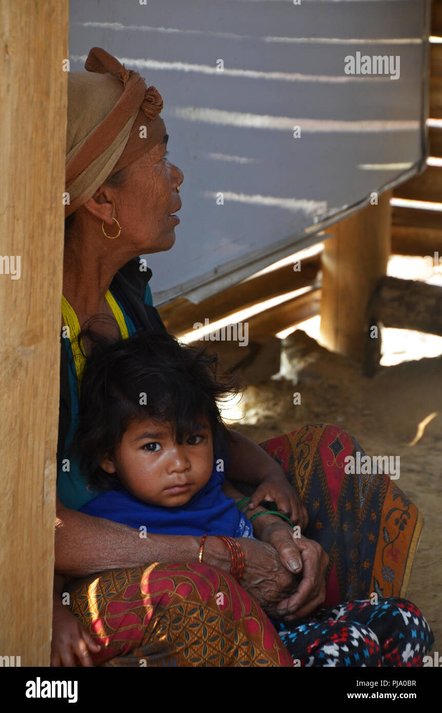 A Dalit (untouchable) girl sits in her mother's lap in the village of Tamakhani, Solukhumbu, Nepal - Stock Image
