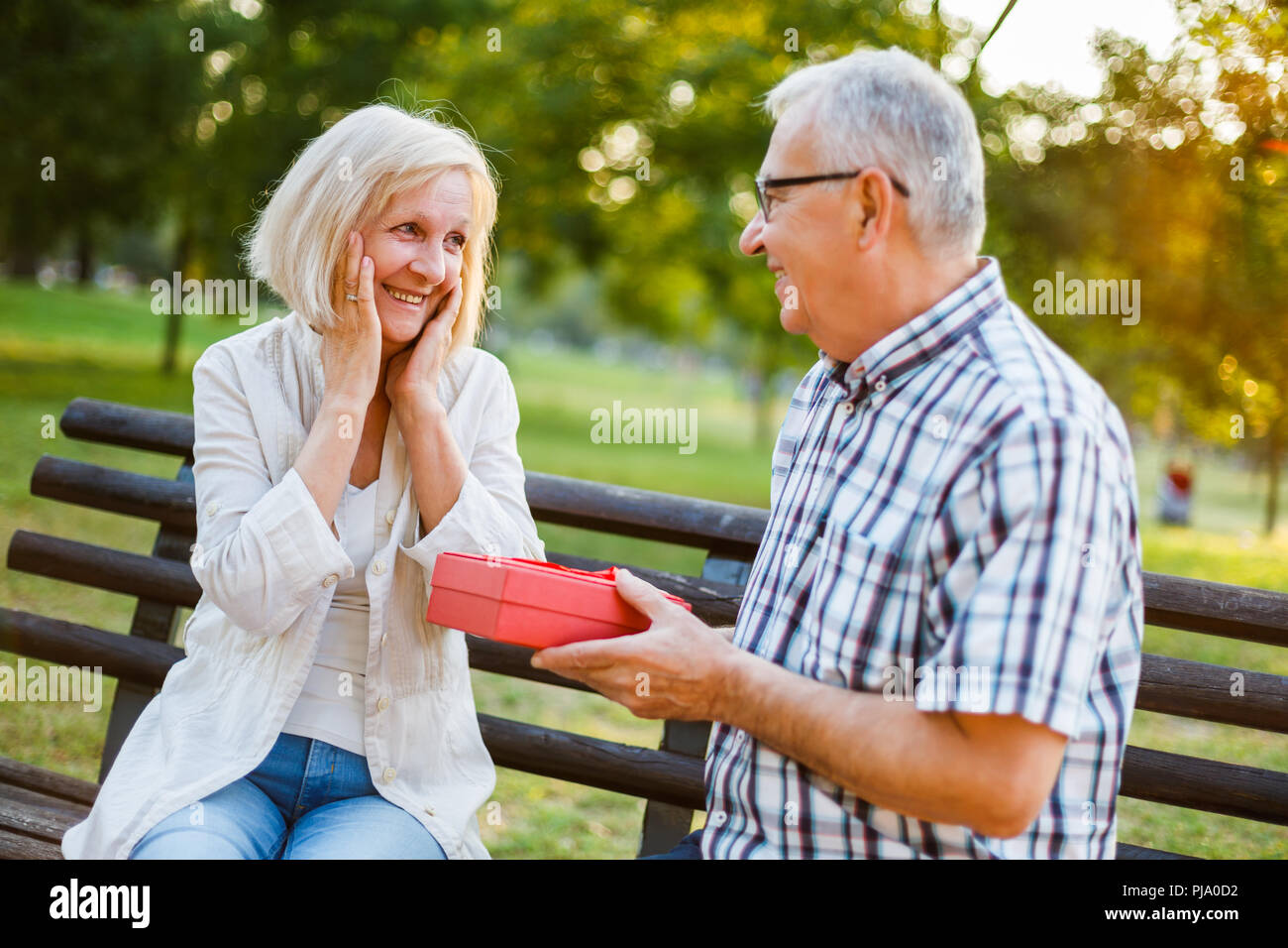 Senior woman is delighted with gift from her man. - Stock Image