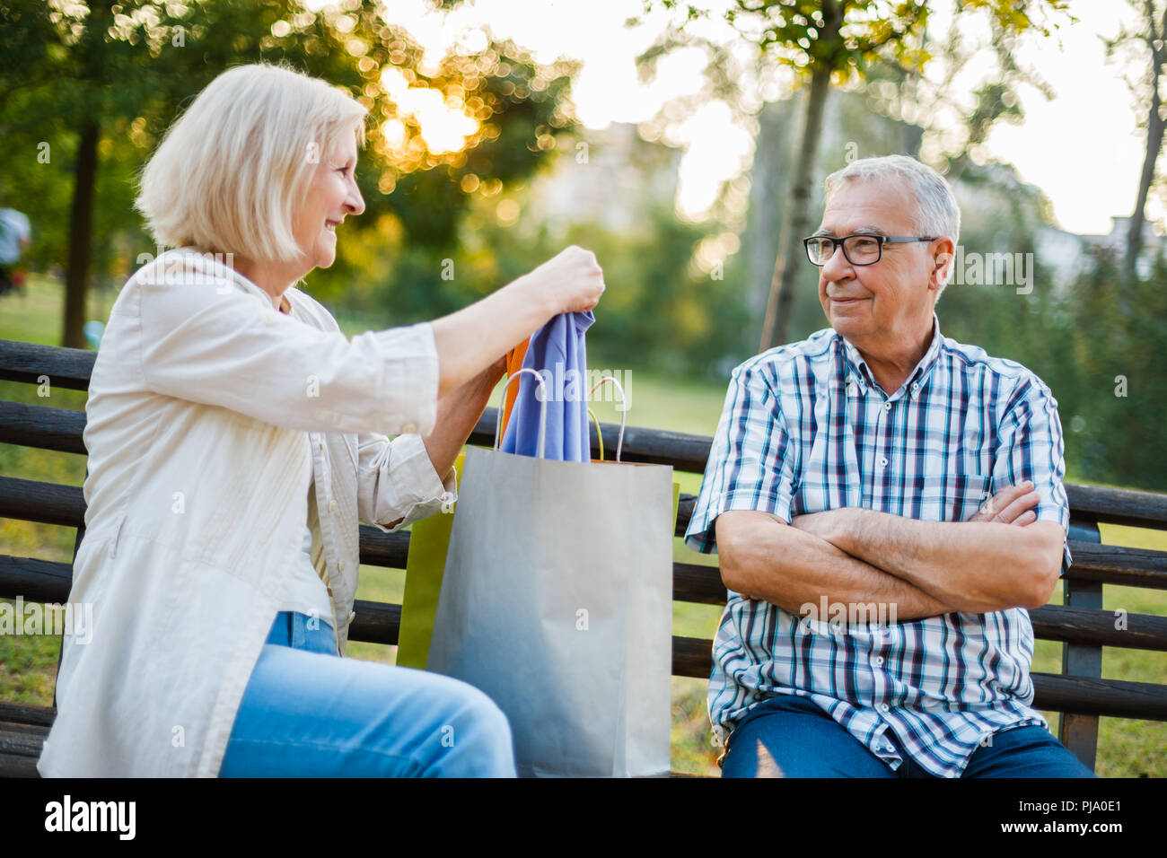Senior man is angry because his woman is spending money on clothes. - Stock Image
