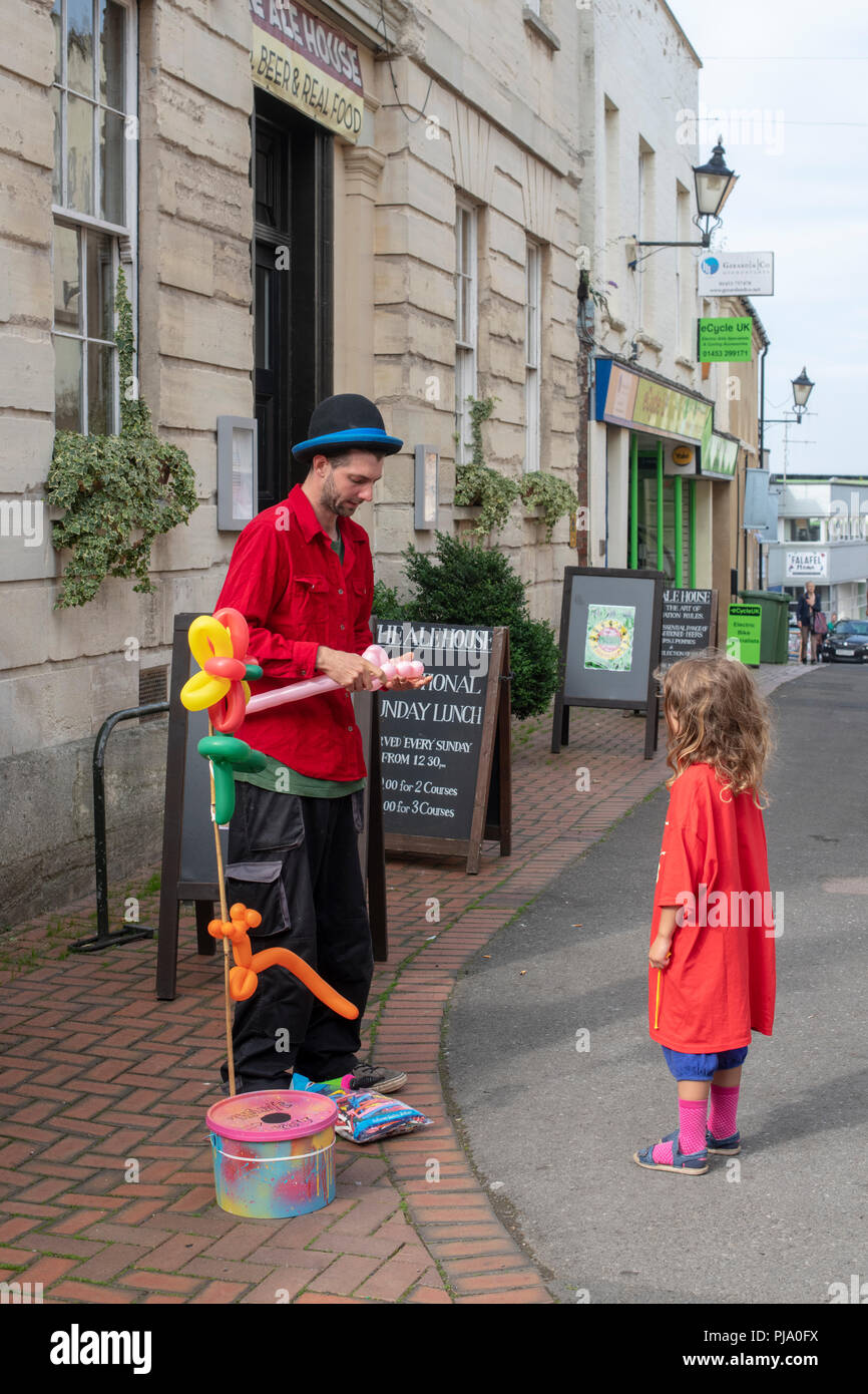 Balloon seller making a balloon animal for a young girl at Stroud farmers market. Stroud, Gloucestershire, England - Stock Image