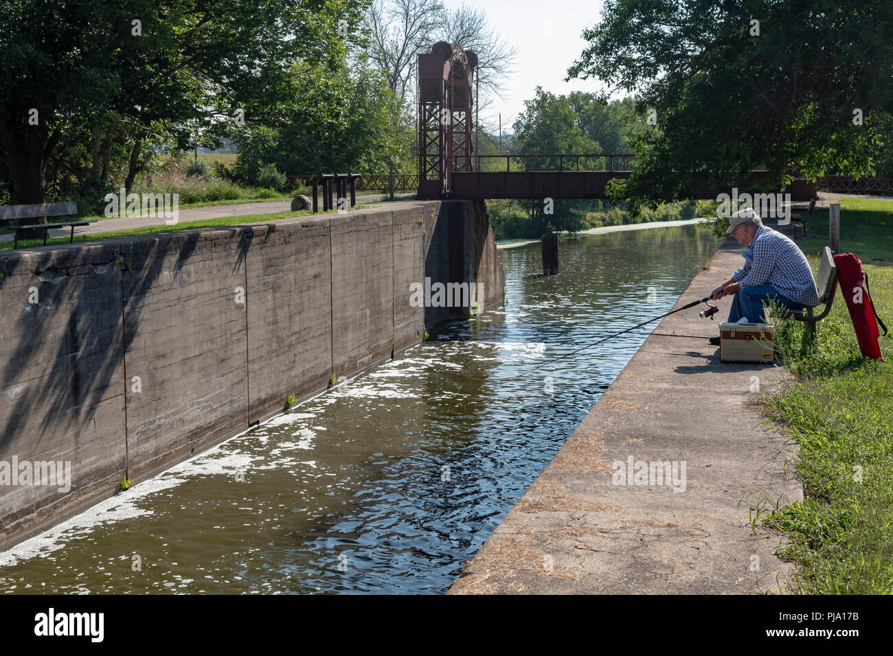 Wyanet, Illinois - A man fishing at Lock 21 of the Hennepin Canal. The canal was completed in 1907 to link the Illinois and Mississippi Rivers, but it - Stock Image