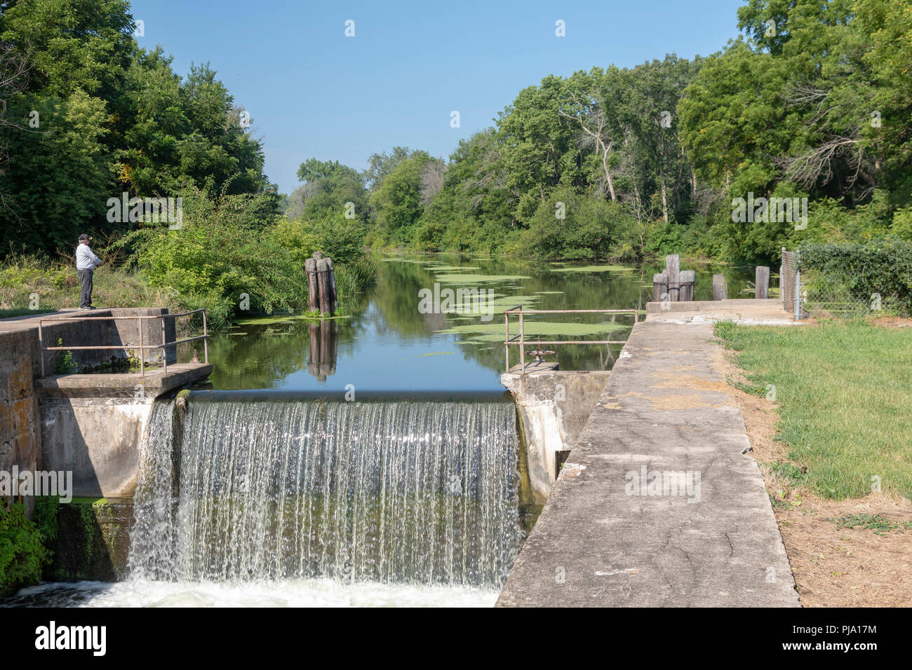 Wyanet, Illinois - A man fishes at Lock 21 of the Hennepin Canal. The canal was completed in 1907 to link the Illinois and Mississippi Rivers, but it  - Stock Image