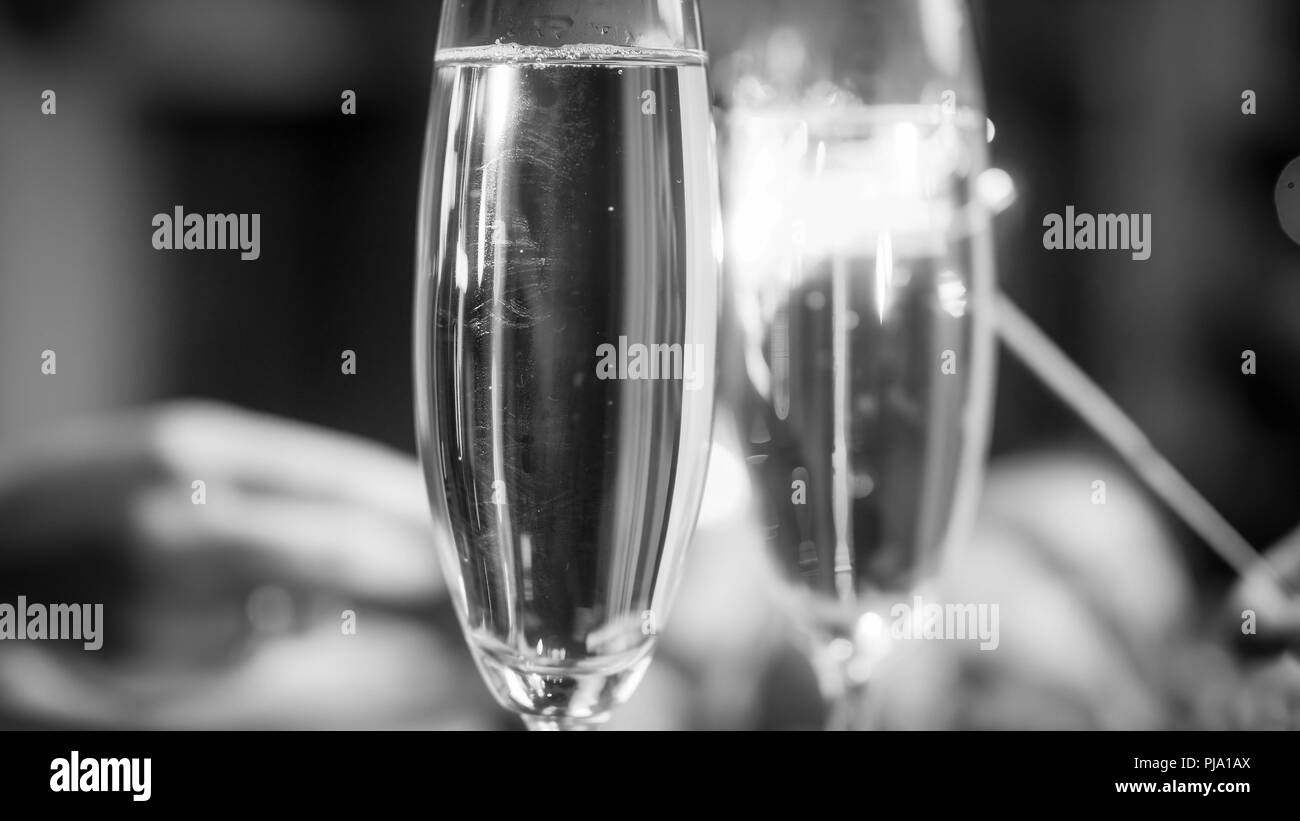 Closeup black and white image of two hands holding sparklers behind two glasses of champagne - Stock Image