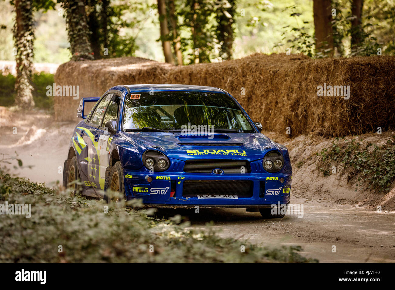 2002 Subaru Impreza WRC with driver Petter Solberg on the forest rally stage at the 2018 Goodwood Festival of Speed, Sussex, UK. - Stock Image