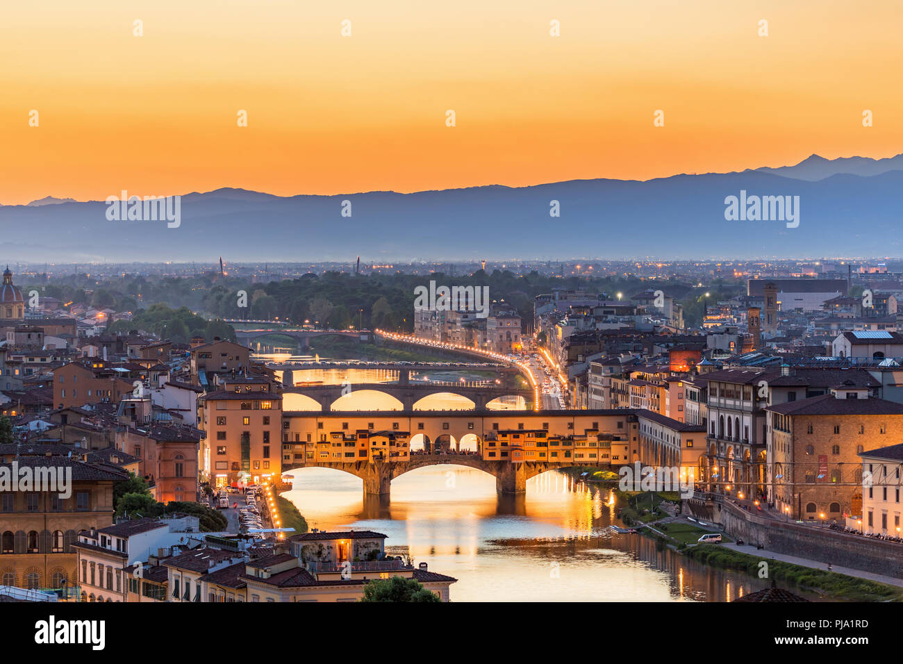 View of Florence at sunset with the Ponte Vecchio bridge over the Arno River - Stock Image