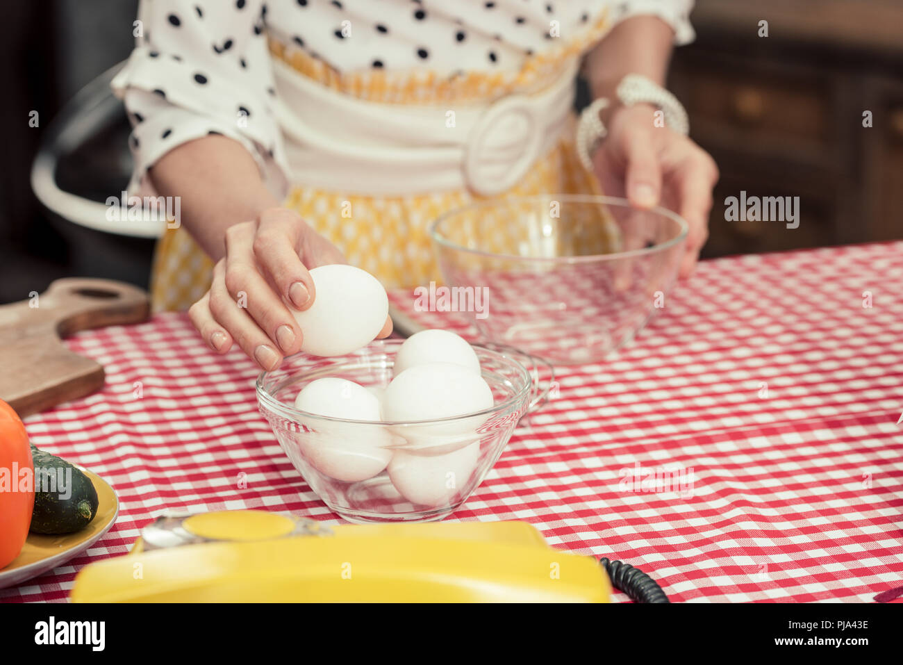 cropped shot of housewife in polka dot shirt with eggs and bowl for omelette - Stock Image