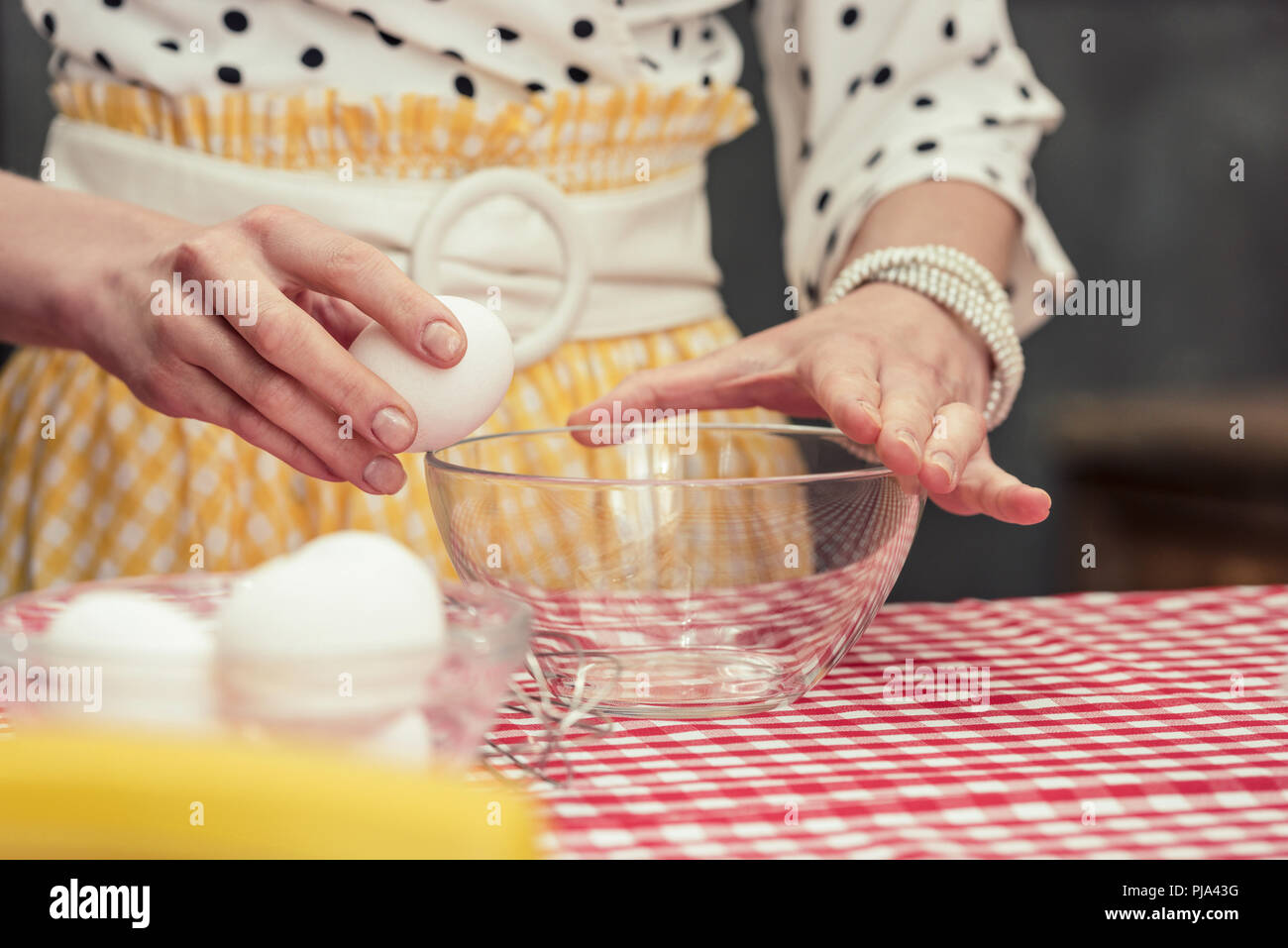 cropped shot of housewife breaking egg into bowl for omelette - Stock Image