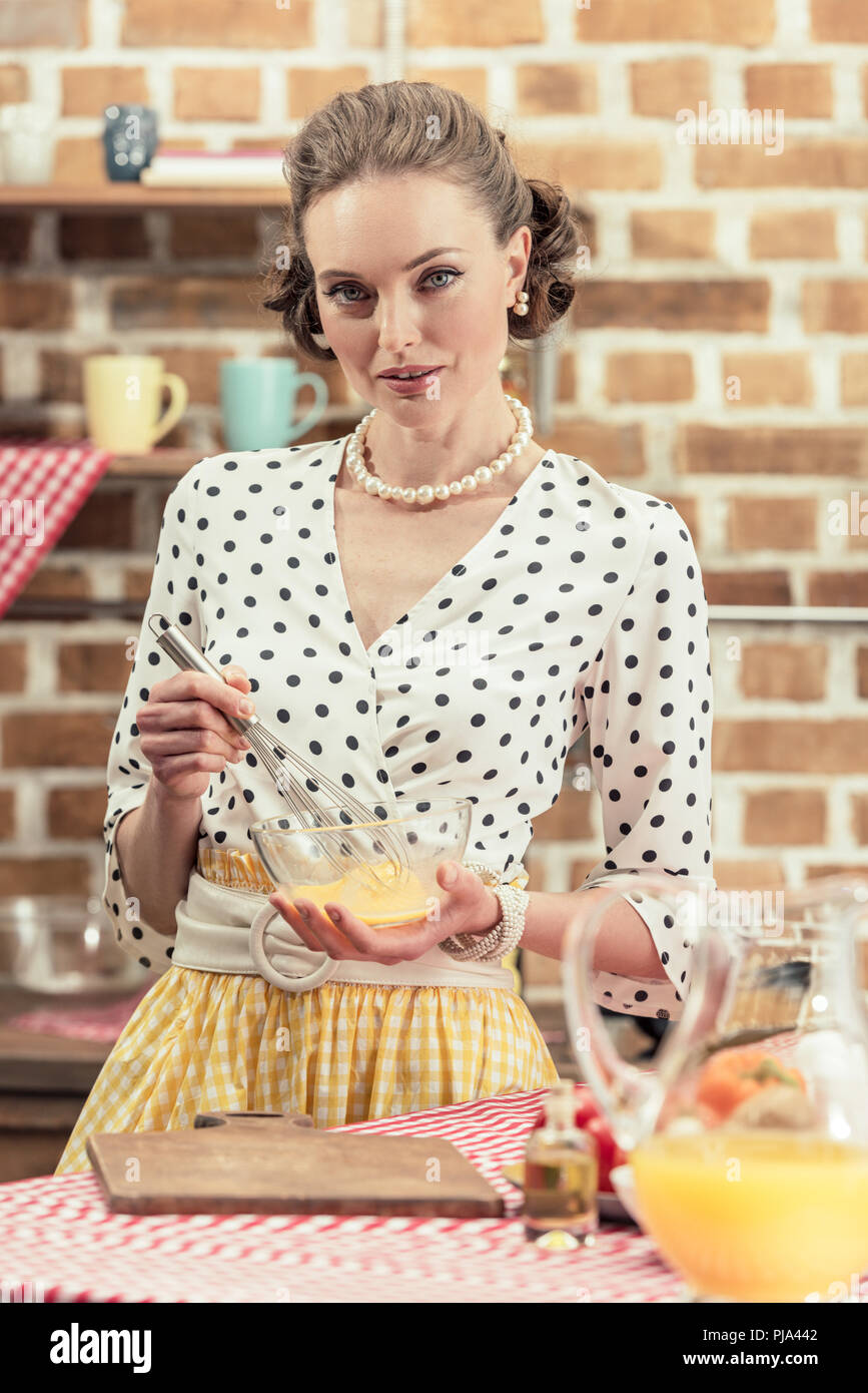 attractive adult housewife whisking eggs for omelette and looking at camera at kitchen - Stock Image