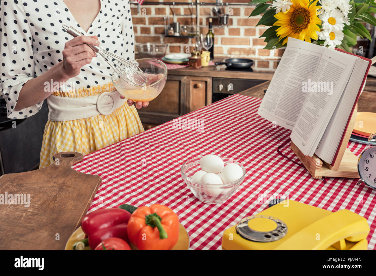 cropped shot of housewife whisking eggs for omelette at kitchen - Stock Image