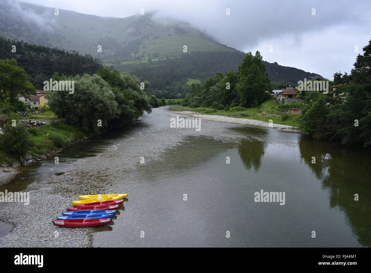 Kayaks by the River Deva in Panes, Picos de Europa, Asturias, northern Spain. Mist is beginning to lift from the hills. - Stock Image